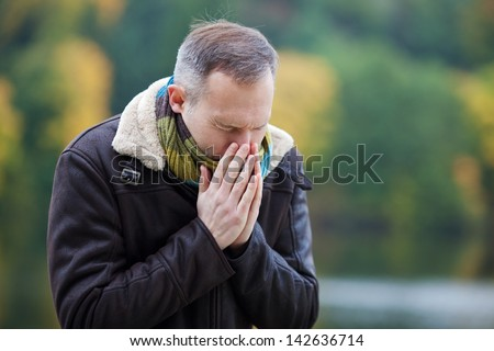 Mature man in jacket suffering from cold