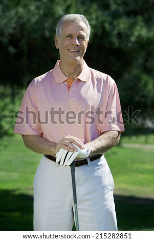 Mature man, in pink short-sleeved shirt and golf glove, standing on golf course, leaning on golf club, smiling, front view, portrait