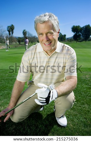 Mature man in striped polo shirt and golf club kneeling on golf course, holding golf club, smiling, front view, portrait