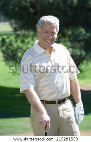 Mature man, in striped short-sleeved shirt and golf glove, standing on golf course, leaning on golf club, smiling, front view, portrait