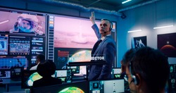 Mature man in suit gesticulating and giving commands to operators while launching rocket with astronaut remotely in flight control station