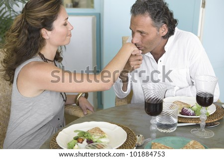 Mature man kissing woman's hand while having a healthy lunch at home.