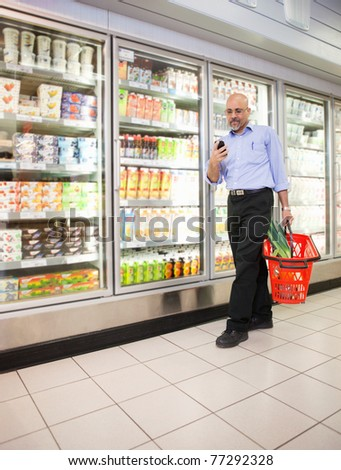 Mature man looking at mobile phone while walking in front of refrigerators in shopping centre
