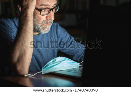 mature man looking on computer at the news about global pandemic from corona virus and he worries, emotional distress, insomnia, concern for business and health in time of covid19 Photo stock ©