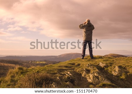 Mature man looking over mountains and hill tops through binoculars.