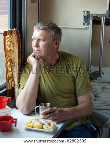 Mature man looking to window in sleeper train