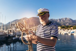 Mature man near the sea dressed in a sailor's shirt and hat holding a sailor rope