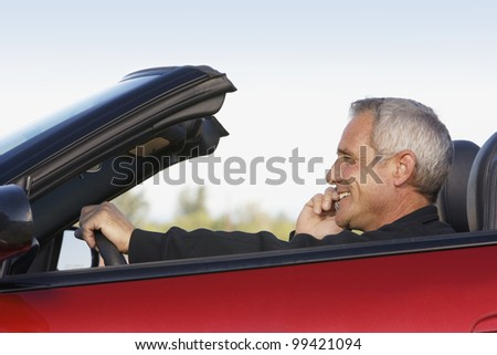 Mature man on cell phone while driving convertible