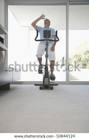 Mature man on exercise bike, pedalling, drinking bottle of water
