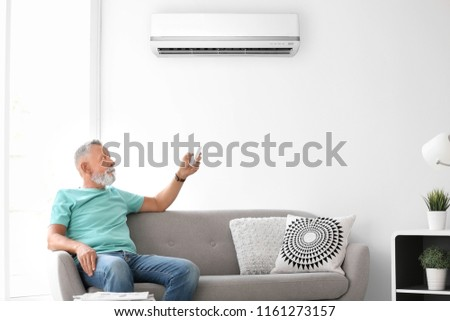 Mature man operating air conditioner while sitting on sofa at home #1161273157
