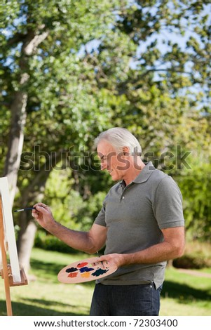 Mature man painting in the garden