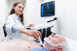 Mature man patient undergoing examination thyroid lying by woman doctor with ultrasonography device