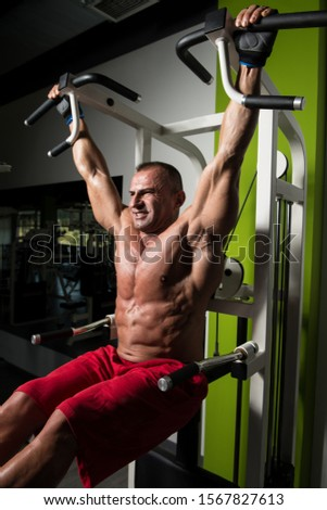 Mature Man Performing Hanging Leg Raises Exercise - One Of The Most Effective Ab Exercises