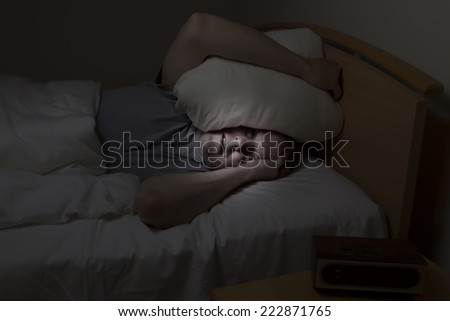 Mature man, pillow over head with eyes wide open, cannot sleep at night from insomnia