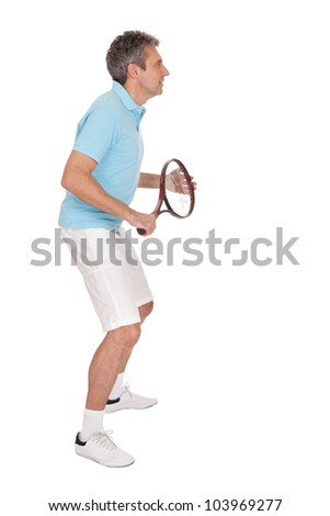 Mature man playing tennis. Isolated on white