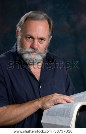 Mature man poses with a serious look with his hand on the bible.