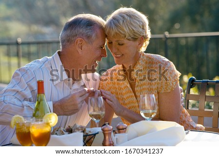 Mature man proposing at outdoor restaurant with engagement ring