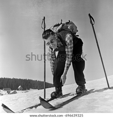 Mature man putting on skis on snowy hill Photo stock ©