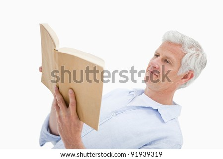 Mature man reading a book against a white background