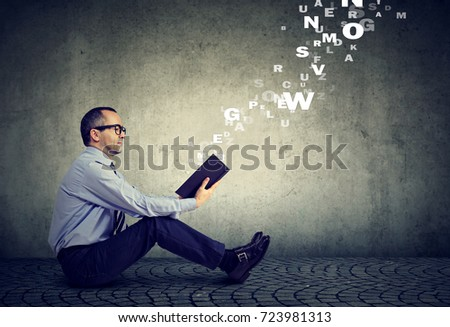 Mature man reading a book with alphabet letters coming out of the book #723981313