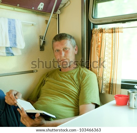 Mature man reading book  in sleeper train