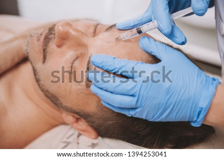 Mature man receiving facial filler injections by professional cosmetologist. Mid-aged man getting anti-wrinkle treatment at beauty salon. Botox, disport filler concept