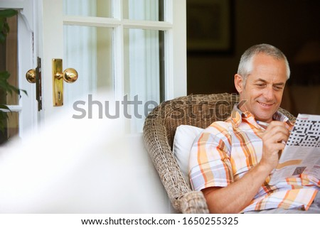 Mature man relaxing in wicker chair at home, doing the crossword in the newspaper