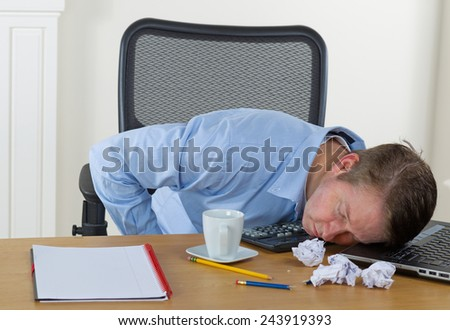 Mature man resting head on laptop with calculator, broken pencils, wadded paper, coffee cup and notepad on desk. Background is white walls.
