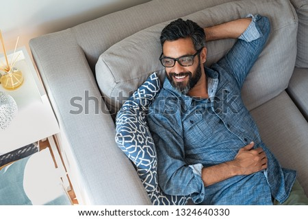 Mature man resting on sofa and thinking about the future. Hispanic man lying on couch and looking away. Smiling casual guy relaxing and daydreaming on sofa at home.