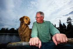 Mature man rowing a boat with a golden retriever