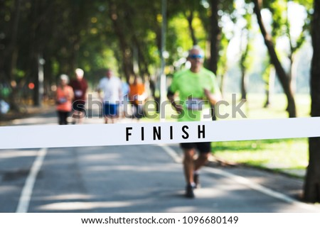 Mature man running towards the finish line #1096680149