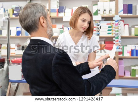 Mature man showing prescription to pharmacist. Customer seeking medicaments for health care. Professional specialist helping client and consulting. Pretty woman wearing in white uniform.