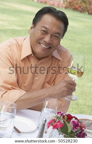Mature man sitting at outdoor table, holding wine glass,