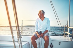 Mature man sitting on the deck of a boat enjoying the day sailing on the open ocean on a sunny afternoon