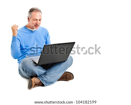 Mature man sitting with his laptop isolated on white
