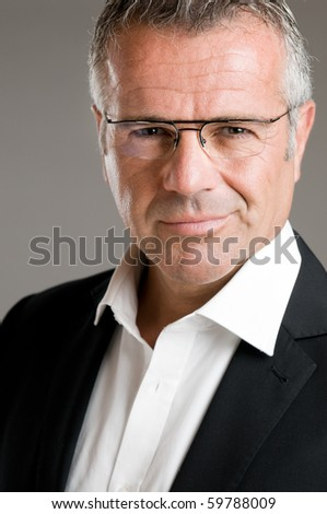 Mature man smile with satisfaction with his new eyeglasses and looking at camera
