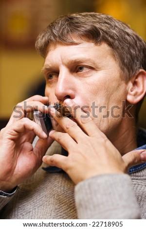 Mature man smoking cigar while speaking on mobile phone