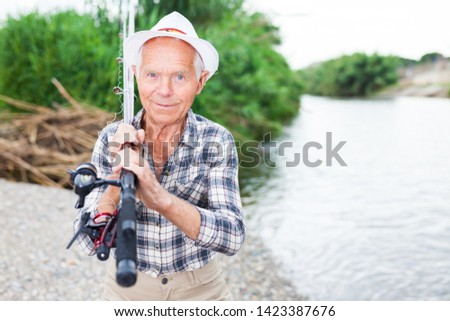 Mature man standing outdoors with angling rod planning to fishing