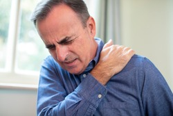Mature Man Suffering With Trapped Nerve In Shoulder At Home