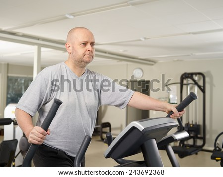 Mature man takes care of his health and he use elliptical trainer in the gym