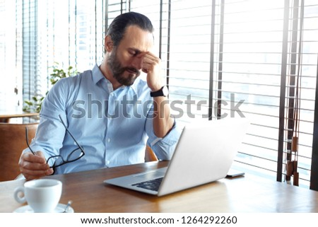 Mature man trader sitting at table at cafe at daytime with cup of coffee and laptop holding eyeglasses closed eyes massaging nose bridge tired