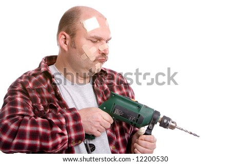 Mature man trying to drill something covered in bandaids