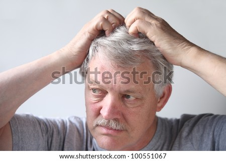 mature man uses both hands to scratch his head