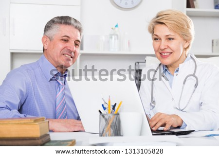 Mature man visits doctor in hospital for consultation on health and treatment  #1313105828
