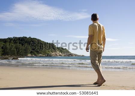 Mature man walking barefoot on a tropical beach in Brazil