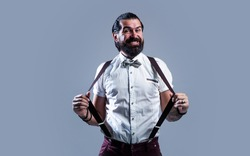 mature man wear suspenders and bow tie has well groomed hair and beard, fashion and barbershop.