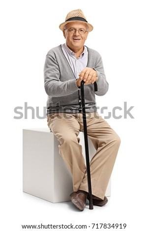 Mature man with a cane sitting on a cube and looking at the camera