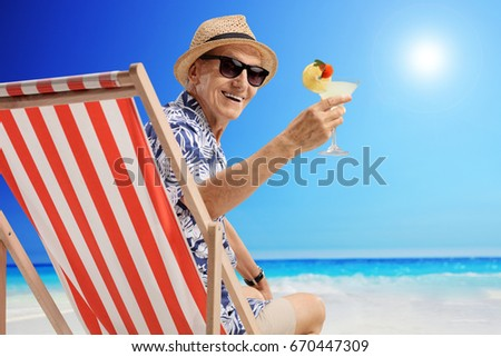 Mature man with a cocktail sitting in a deck chair on a beach #670447309