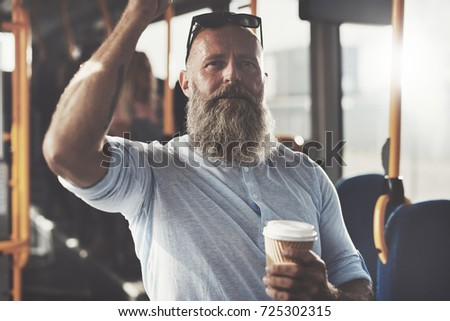 Mature man with a long beard smiling and drinking a takeaway cup of coffee while standing on a bus during his morning commute #725302315