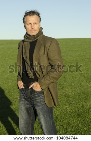 mature man with beard wearing a green scarf and jacket and standing alone in a field.